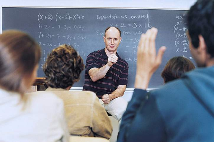 Male Teacher Asking Students Questions During Seminar