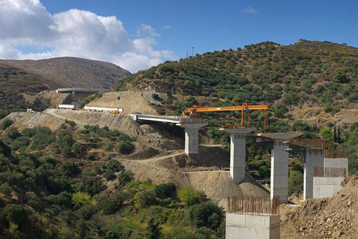 A bridge being constructed around a mountain
