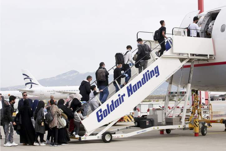 Migrants entering an airplane