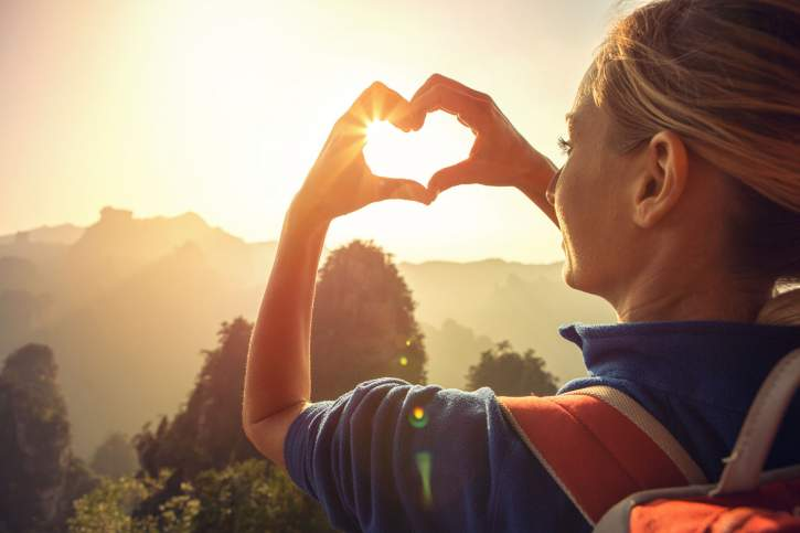 Young woman hiking in the mountains, makes a heart shape finger frame