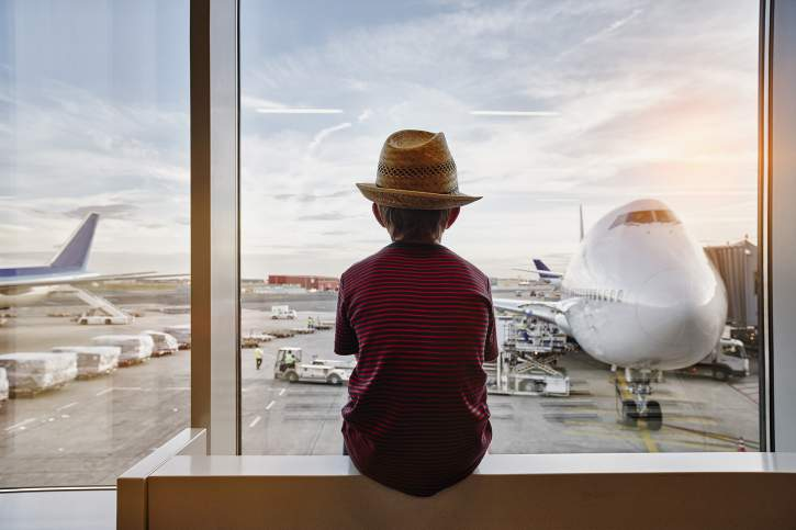 Child gazing the airplanes in the airport